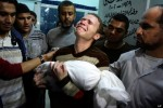 Jihan Misharawi holds the body of his child Omar.